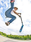 Boy with scooter is going airborne — Stock Photo