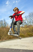 Boy going airborne with a scooter — Stock Photo