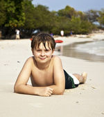 Happy boy lying at the beach — Stock Photo