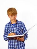 Lycklig smart pojke är att skriva en bok — Stockfoto