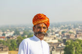 Rajasthani man with bright red turban and bushy mustache poses f — Stockfoto