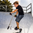 Boy enjoys jumping with his scooter in the halfpipe — Stock Photo #19021211