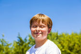 Happy smiling boy enjoys life under blue sky — Stock Photo