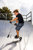 Boy enjoys jumping with his scooter in the halfpipe — Stock Photo