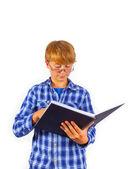 Szczęśliwy inteligentny chłopiec czyta w książce — Zdjęcie stockowe