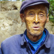 Old farmer in traditional blue working class uniform — Stockfoto