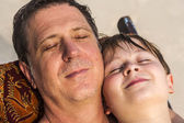 Father is spooning with his happy smiling son — Stock Photo