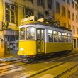 Traditional yellow tram downtown Lisbon by night - Stock Photo