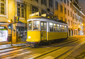 Traditional yellow tram downtown Lisbon by night — Stock Photo