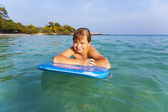 Boy is swimming on his surfboard and happily smiling in a beautiful sea with crystal clear water and blue sky — Stock Photo