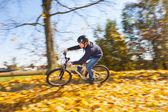 Boy jumps rides his bicycle with speed in open area and enjoys r — Stock Photo