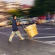 Man carries a straw crate on a sack barrow — Stock Photo