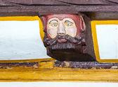 Hout snijwerk met grappige gezichten op hout balk van oude kader h — Stockfoto