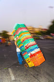 Man carries plastic crates on a sack barrow — Stock Photo