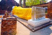 Leżący Budda ubrany w żółty szalik w świątyni wat yai chai-mong — Zdjęcie stockowe