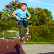 Boy jumps with scooter at the skate park over a ramp — Stock Photo