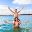 Stock Photo: Boys have fun playing piggy-back in ocean