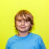 Happy smiling young boy with yellow wall — Stockfoto