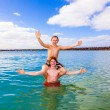 Stock Photo: Boys have fun playing piggyback in clear sea