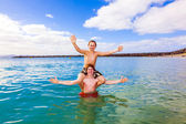 Boys have fun playing piggyback in the clear sea — Stock Photo
