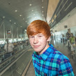 Young boy on a moving staircase inside the airport — Stock Photo #19835183