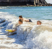 Boys have fun surfing in the waves — Stock Photo