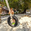 Boy climbinmg in a tire and swinging at the beach - Stock Photo