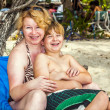 Royalty-Free Stock Photo: Mother hugging with young son in the beach chair