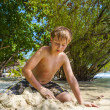 Happy young boy is digging in the sand of the beach and construc — Stock Photo #20167611