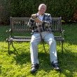 Old man enjoys sitting on a bench in his garden — Stock Photo #20505363
