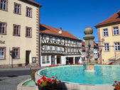 Market place wit fountain and half timbered houses in fairy tal — Stock Photo