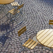 Outdoor German cafe seating with round tables and wooden   chair - Stock Photo