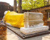 Lying Buddha dressed in yellow scarf — Stock Photo