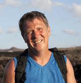 ランサローテ島の火山地域を通じてトレイルを歩く男 — ストック写真