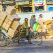 Rickshaw rider transports heavy goods early morning — ストック写真