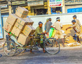 Rickshaw rider transports heavy goods early morning — Stock Photo
