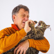 Cat trying to catch the glasses of a man — Stock Photo #22377741