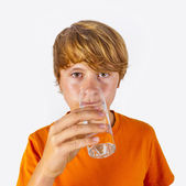Cute boy with orange shirt drinks water — Stock Photo