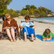 Stock Photo: Family is enjoying the sun and relaxing and reading books at the