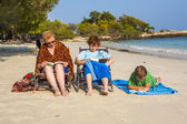 Family is enjoying the sun and relaxing and reading books at the — Stock Photo