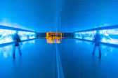 Tunnel with pedestrians in motion in blue cool light — Stock Photo