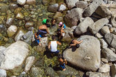 Tourists cool their legs in the lake of the lower Yosemite wate — Stock Photo