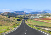 Driving in Lanzarote with view to Timanfaya volcanoes — Stock Photo
