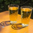 Cidre glasses standing on an outdoor table in the sun as symbol — Stockfoto