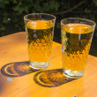 Cidre glasses standing on an outdoor table in the sun as symbol - Stock Photo