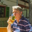 Thirsty man drinks out of a glass in the outdoor garden - Foto Stock