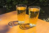 Cidre gafas de pie sobre una mesa al aire libre bajo el sol como símbolo — Foto de Stock