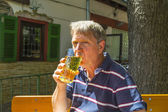Thirsty man drinks out of a glass in the outdoor garden — Stok fotoğraf