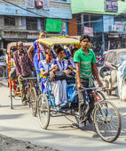 Rickshaw rider transports passenger in Old Delhi, India. — Stock Photo