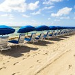 Stock Photo: Umbrellas and empty beach couches at beach
